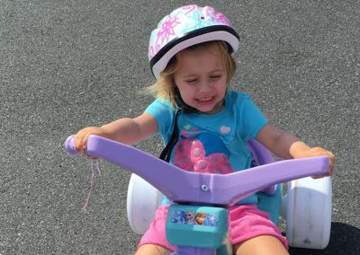 Girl riding big wheel tricycle