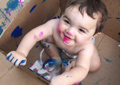 Toddler in box finger painting