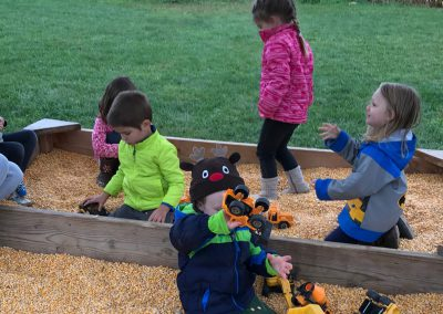 Children playing outside in sandbox